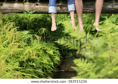 Young couple dangling their feet from wooden bridge over small creek. - stock photo