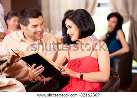 young couple deciding menu order restaurant table - stock photo