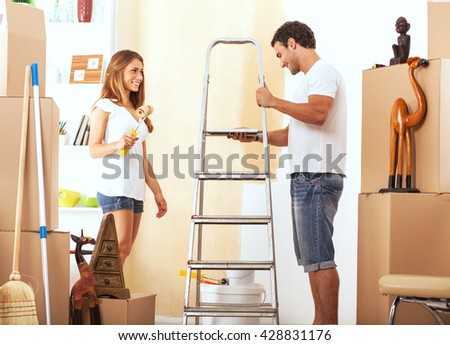 Young couple decorate their new apartment.They painted the wall. - stock photo