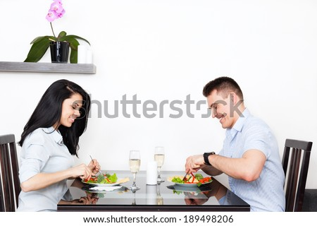 Young couple dinner at table, eat food, romantic date at restaurant, home or cafe - stock photo