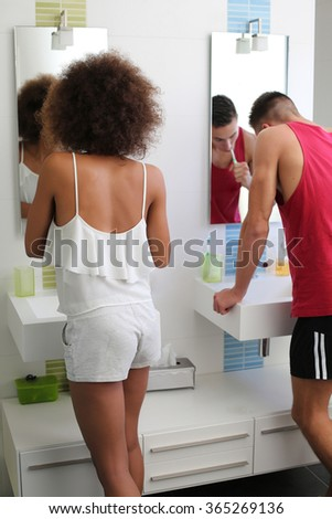 young couple do one's teething bathroom front of mirrors. - stock photo