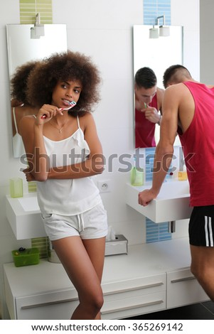young couple do one's teething bathroom front of mirrors.