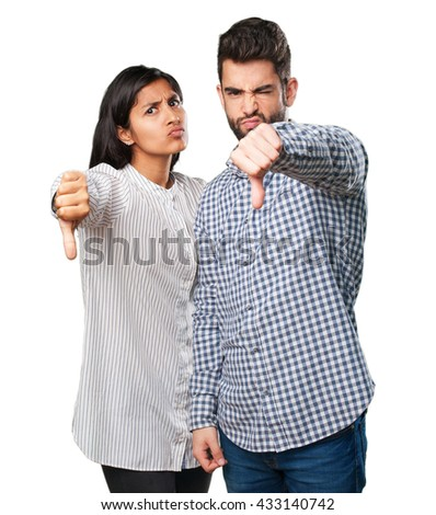 young couple doing a thumb down gesture - stock photo