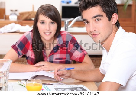Young couple doing coursework at the kitchen table - stock photo