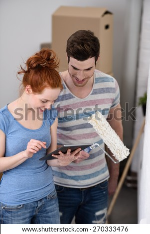 Young couple doing DIY painting their new house pausing to use a tablet reading their social media with a smile - stock photo