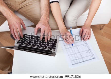 Young couple doing family finances at laptop at home - stock photo
