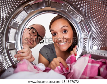 Young couple doing laundry View from the inside of washing machine.  - stock photo