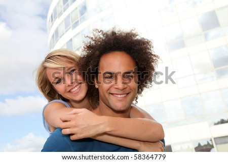Young couple doing piggyback outside