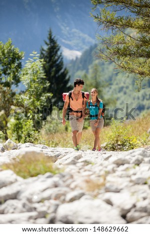 Young couple doing trekking in the mountains while looking around - stock photo