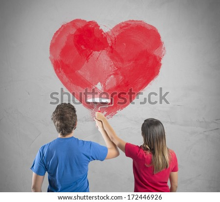 Young couple drawing a big heart in a wall - stock photo