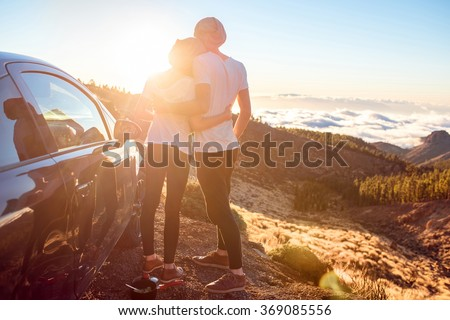 Young couple dressed alike in white t-shirt and hat embracing near the car on the roadside on the sunset. - stock photo