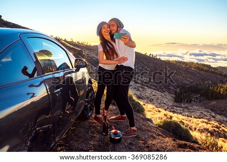 Young couple dressed alike in white t-shirt and hat taking selfie photo with samrt phone near the car on the roadside on the sunset. - stock photo