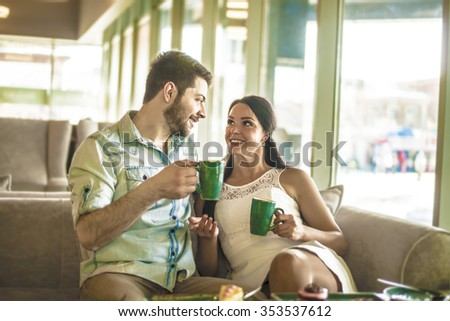 young couple drink coffee with handsome man look in eyes each other girl friend Woman look at cake Near together against glass window view in perspective Happy couple enjoy coffee at coffee shop cafe - stock photo