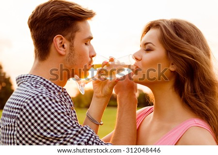 young couple drinking champagne at sunset - stock photo