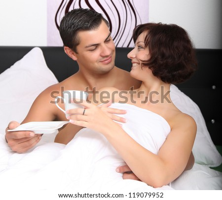 young couple drinking coffee in bed - stock photo