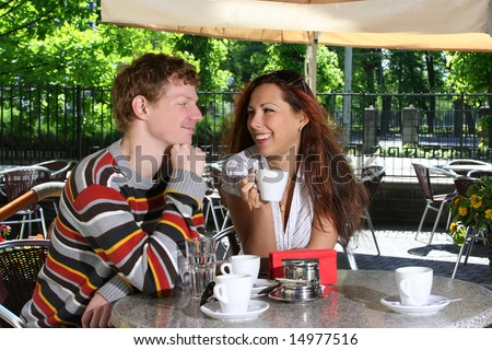 young couple drinking coffee in open-air cafe - stock photo