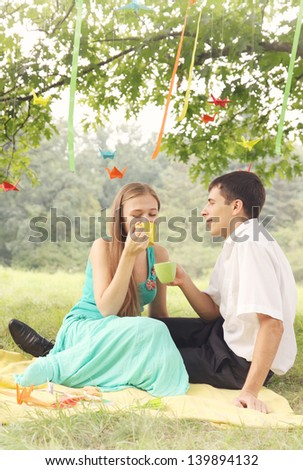 Young couple drinking hot tea in the park - stock photo