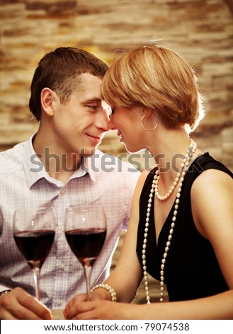 Young couple drinking wine and flirting - stock photo