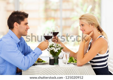 young couple drinking wine in modern restaurant - stock photo