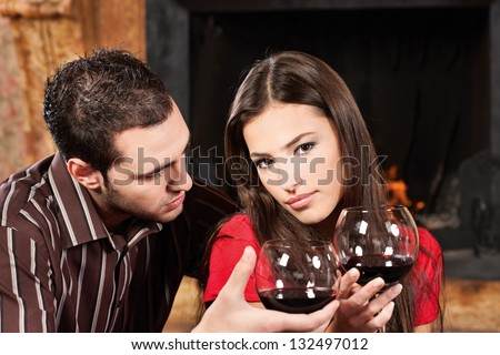 Young couple drinking wine near fireplace - stock photo