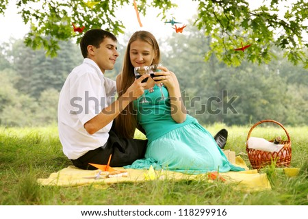 Young couple drinking wine under a tree - stock photo