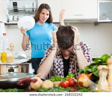 Young couple during quarrel in kitchen at home. Focus on girl  - stock photo