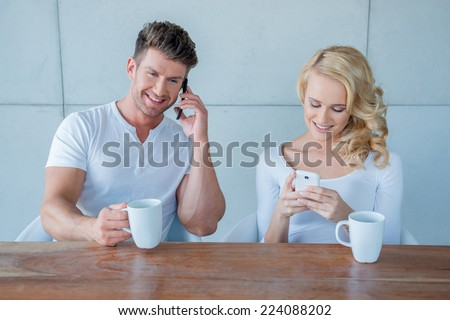 Young couple each using their mobile phone as they sit drinking their morning coffee with the husband making a call and the wife texting a message - stock photo