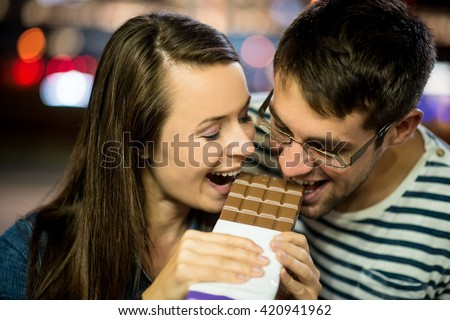 Young couple eat together chocolate on date - in street at night