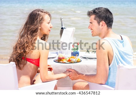 Young couple eating at beach restaurant with blue ocean view - Teenagers romantic  lunch time moment on resort terrace with sea background - Summer concept of love and life joys - Sunny day lights - stock photo