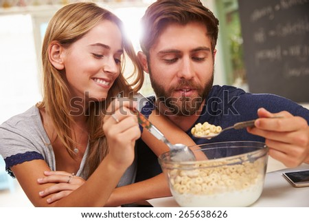 Young Couple Eating Breakfast In Kitchen Together - stock photo