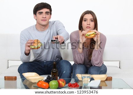 Young couple eating burgers - stock photo