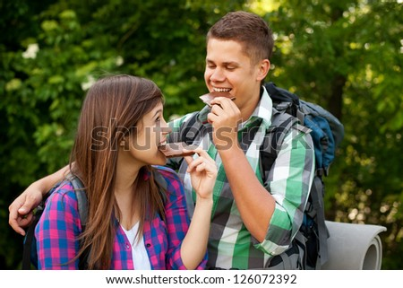 Young couple eating chocolate in forest - stock photo