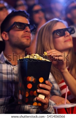 Young couple eating popcorn in multiplex movie theater, watching 3D movie. Focus on popcorn. - stock photo
