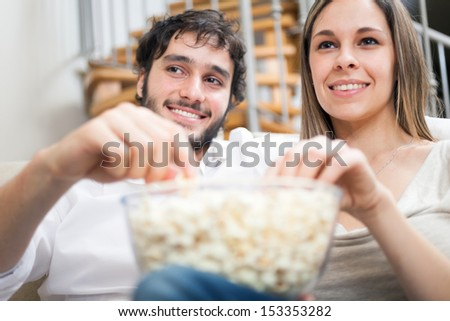 Young couple eating popcorn while watching a movie - stock photo