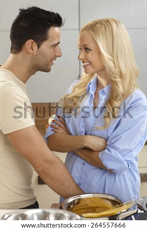 Young couple, eating the same spaghetti, looking at each other in kitchen with love, smiling. - stock photo