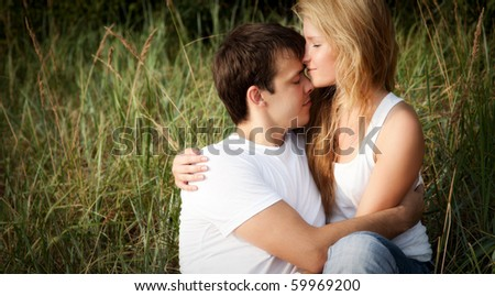 young couple embrace in high grass - stock photo