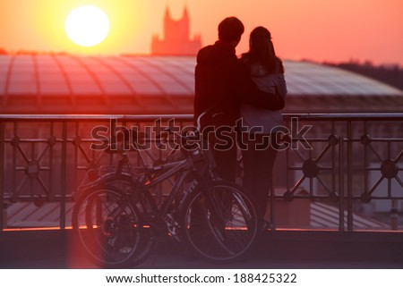 Young couple embracing and enjoying beautiful sundown in the city from the viewing point - stock photo