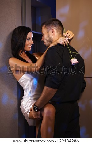 Young couple embracing and kissing at home, leaning against wall, smiling. - stock photo