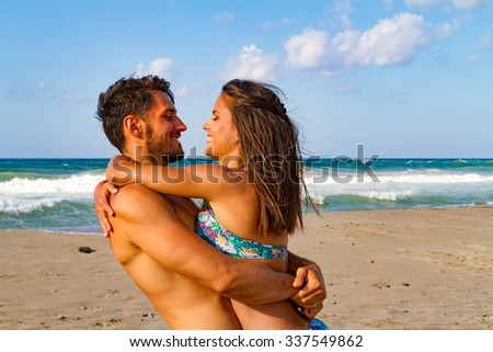 Young couple embracing and kissing at the beach in late summer at dusk. - stock photo