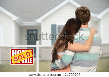 Young couple embracing in front of house with sold sign - stock photo