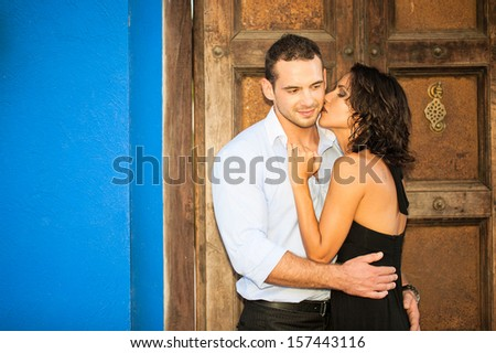 Young couple embracing outdoors, smiling - stock photo