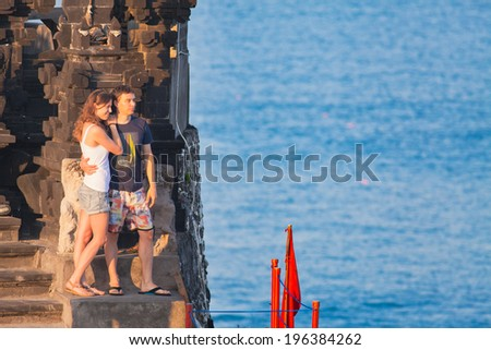 young couple embracing stands on a cliff above the ocean. Indonesia, Bali - stock photo