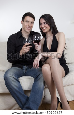 Young couple enjoy red vine, at home, sitting on the white sofa