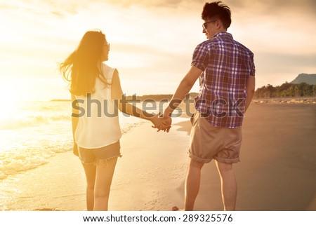 young couple enjoying a beach walk at sunset - stock photo