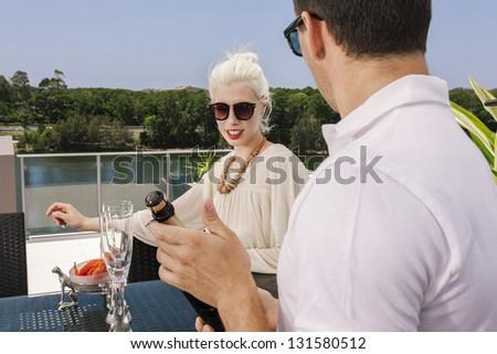 Young couple enjoying a drink on modern balcony - stock photo