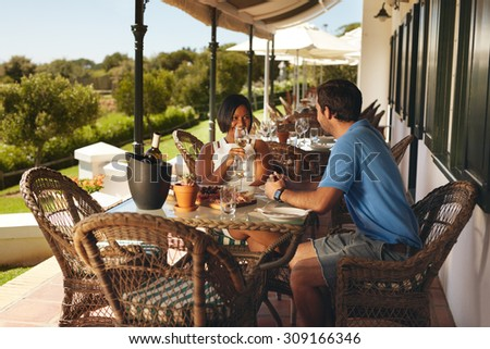 Young couple enjoying a glass of wine. Man and woman on holiday drinking wine at winery restaurant. - stock photo