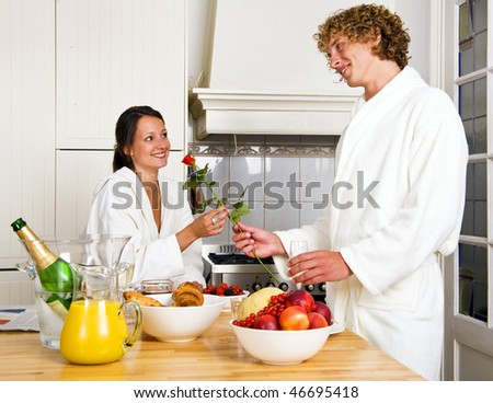 Young couple enjoying a luxurious champagne breakfast on a sunday morning - stock photo