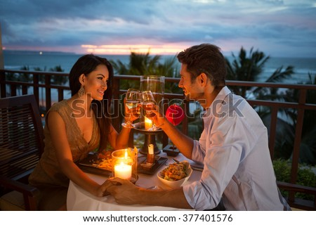 young couple enjoying a romantic dinner by candlelight, outdoor - stock photo
