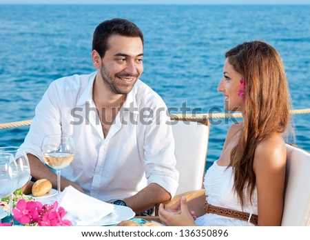 Young couple enjoying a romantic meal sitting at a table at a waterfront restaurant talking to each other with an ocean backdrop - stock photo