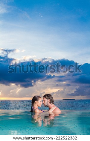 Young couple enjoying a romantic swim standing chest deep in the sea facing each other in an intimate embrace copyspace in the sky - stock photo